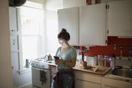 Smiling woman texting with cell phone in kitchen - HEROF25337