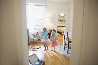 Sisters in tutus dancing in living room - HEROF25343