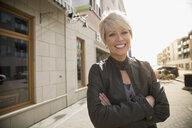 Portrait of smiling blonde woman on urban street - HEROF25373