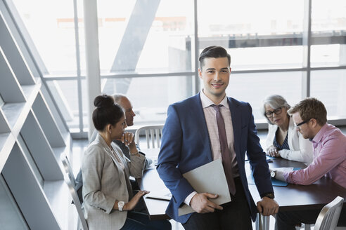 Portrait of confident businessman in conference room meeting - HEROF25448