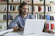 Architect using laptop over blueprints - HEROF25478