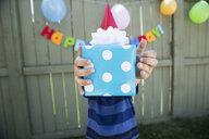 Boy holding polka-dot wrapped birthday gift - HEROF25511