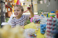 Boy wearing birthday party hat holding candy - HEROF25517