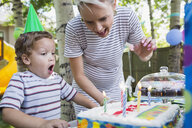 Boy blowing out birthday candles on cake backyard - HEROF25520
