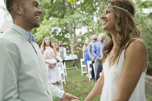 Bride and groom holding hands at backyard wedding - HEROF25535