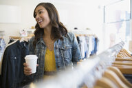 Woman with coffee in clothing shop - HEROF25598