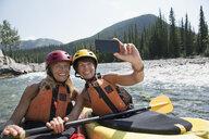 Women taking selfie kayaking in river - HEROF25607