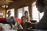 Young friends hanging out in cabin living room - HEROF25682
