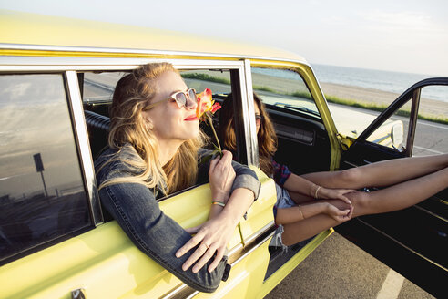Young Woman Sitting With Friend In Car At Beach - TGBF01967