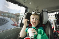 Cute boy licking drinking straw while sitting on vehicle seat in car - CAVF60635