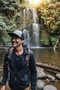 Smiling hiker standing against waterfall in forest - CAVF60668