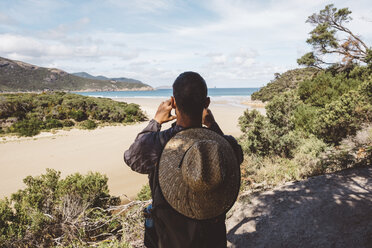 Rear view of hiker with backpack and straw hat photographing sea while standing in forest at Wilsons Promontory National Park - CAVF60680