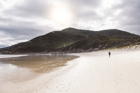 Mid distance view of hiker walking at beach towards mountains against cloudy sky - CAVF60686