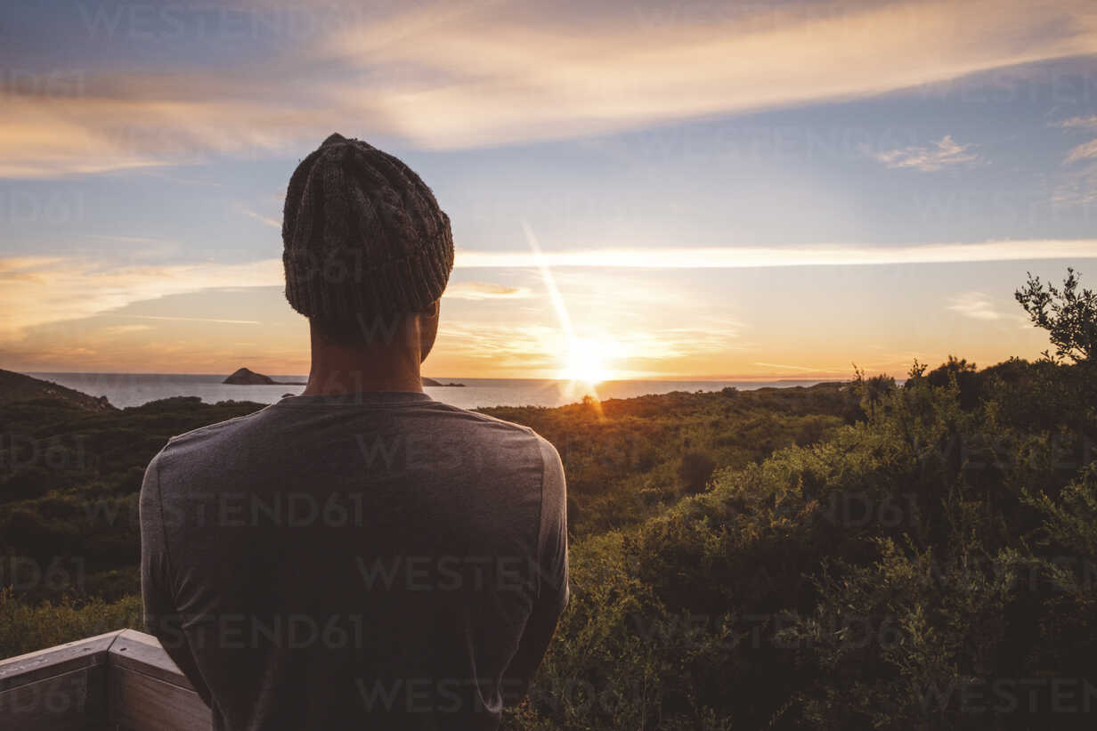 Rear view of man wearing knit hat looking at sea against sky during sunset - CAVF60698 - Cavan Images/Westend61