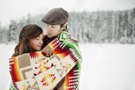 Romantic couple wrapped in blanket while standing at snow covered forest - CAVF60725