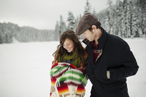 Happy couple looking at blanket while standing in snow covered forest - CAVF60728