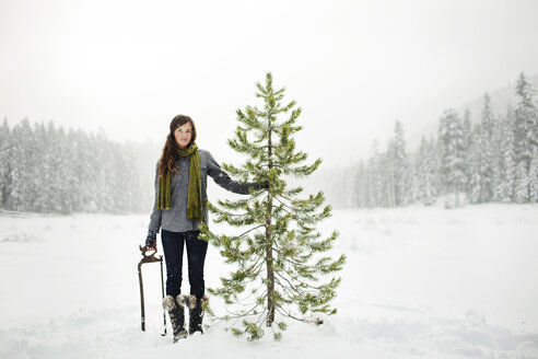 Portrait of woman holding pine tree while standing on snow covered field against sky in forest - CAVF60731