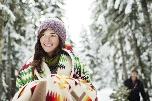 Close-up of girlfriend looking away while standing against boyfriend in snow covered forest - CAVF60734
