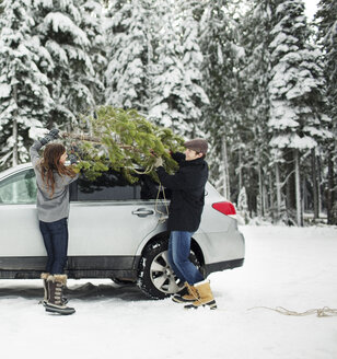 Couple putting pine tree on car roof while standing in snow covered forest - CAVF60737