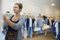 Woman browsing in clothing shop - HEROF25809