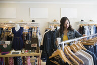 Woman browsing clothing in shop - HEROF25812
