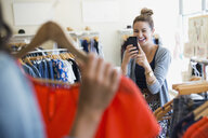 Woman photographing friend holding shirt in clothing shop - HEROF25815