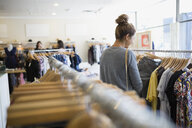 Woman browsing clothing rack in shop - HEROF25821