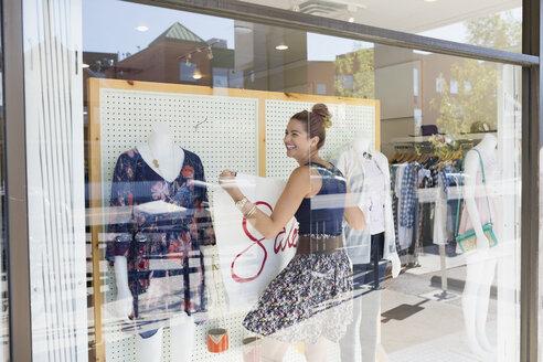 Smiling worker hanging sale sign clothing shop window - HEROF25824