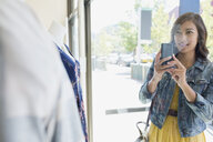 Smiling woman photographing shop window display camera phone - HEROF25827