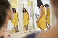 Woman trying on dress at windows clothing shop - HEROF25830