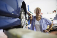 Smiling female mechanic leaning on car - HEROF25833