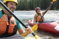 Smiling couple kayaking in river - HEROF25845
