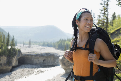 Smiling woman backpacking above river - HEROF25854