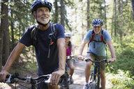 Smiling senior man mountain biking in woods - HEROF25869