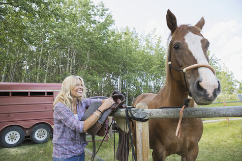 Smiling woman with horse in pasture - HEROF25881