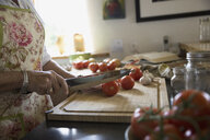 Woman cutting tomatoes on cutting board - HEROF25896