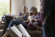 Smiling senior women enjoying book club on sofa - HEROF25899