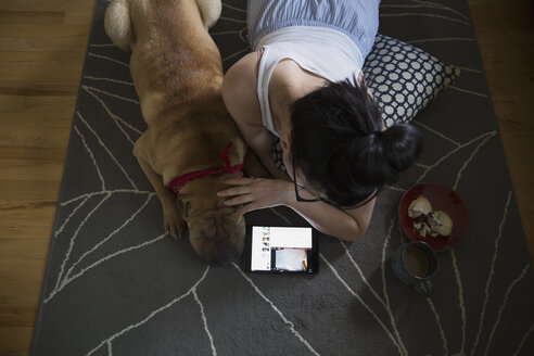 Woman and dog using digital tablet on floor - HEROF25929