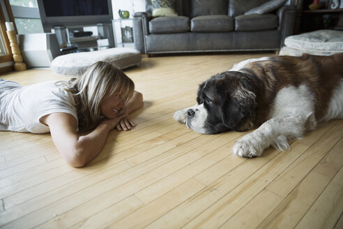 Woman and dog laying face to face floor - HEROF25956