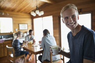 Smiling young man drinking coffee with friends cabin - HEROF25974