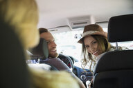 Smiling young friends riding in car - HEROF25995