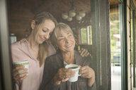 Smiling mother daughter drinking coffee cabin screen door - HEROF26004