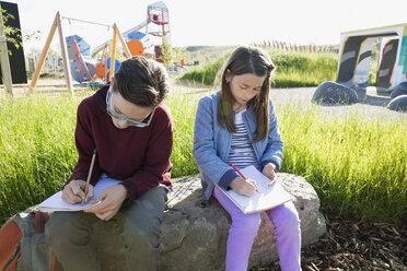 Students doing homework on rock near sunny playground - HEROF26031