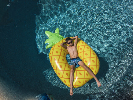 High angle view of shirtless boy with hands behind head relaxing on inflatable ring in swimming pool - CAVF60798