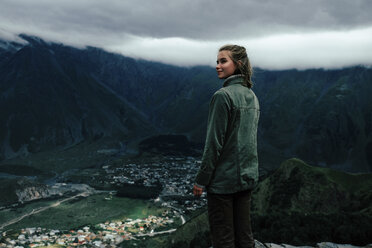 Side view of woman looking away while standing on mountain against cloudy sky - CAVF60807