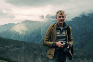 Portrait of confident man holding camera while standing on mountain against cloudy sky - CAVF60810