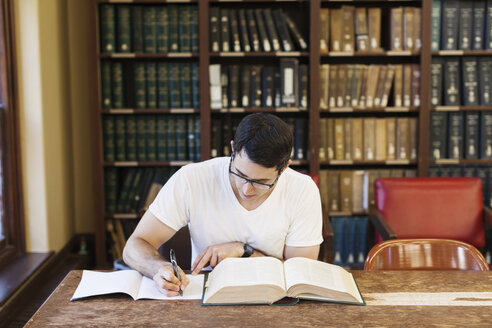 Confident male student studying in library - CAVF60813