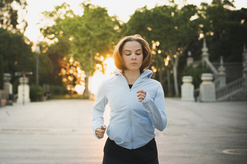Woman jogging while exercising in park during sunrise - CAVF60825