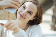Smiling woman taking selfie with smart phone in city - CAVF60828
