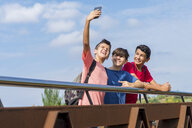 Schoolboy taking selfie with friends while standing by railing on footbridge against sky during sunny day - CAVF60873